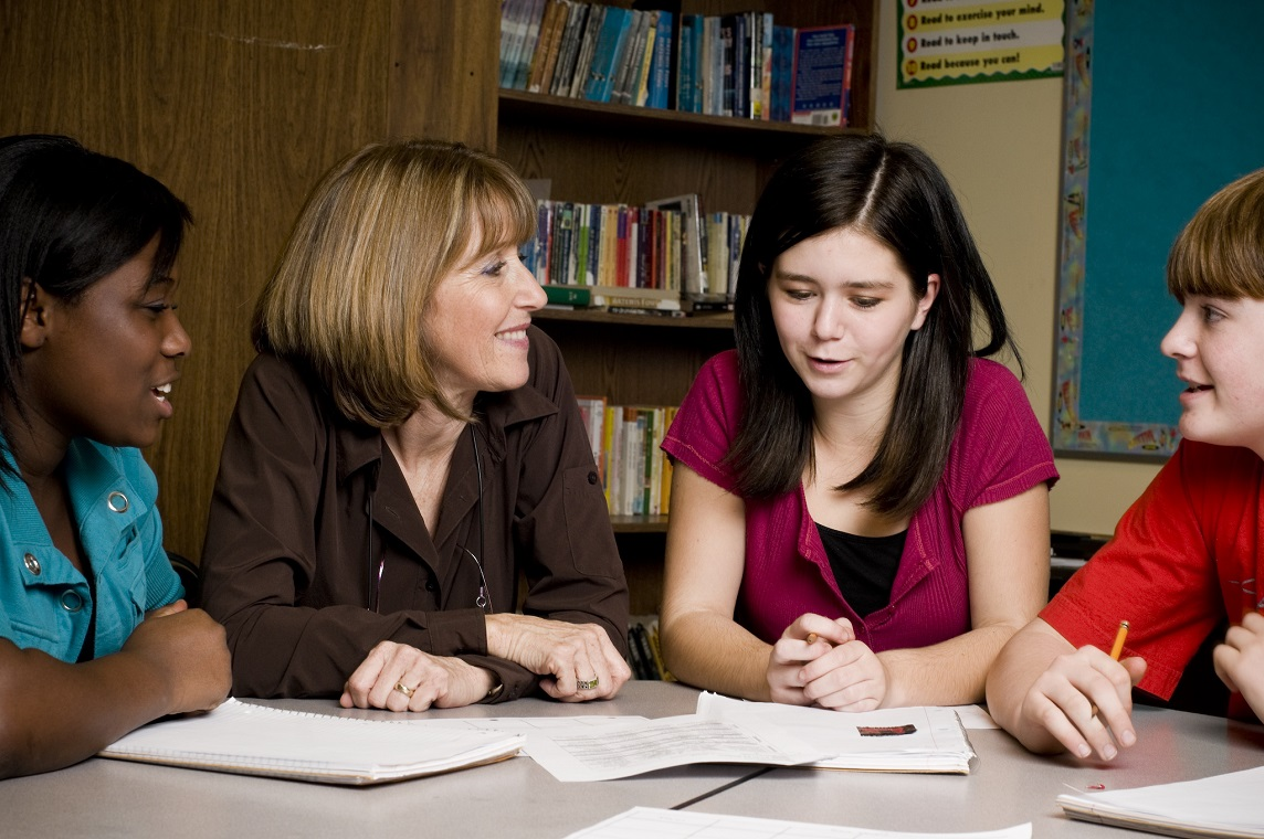 An image showing a Teaching Assistant working with a small group of students