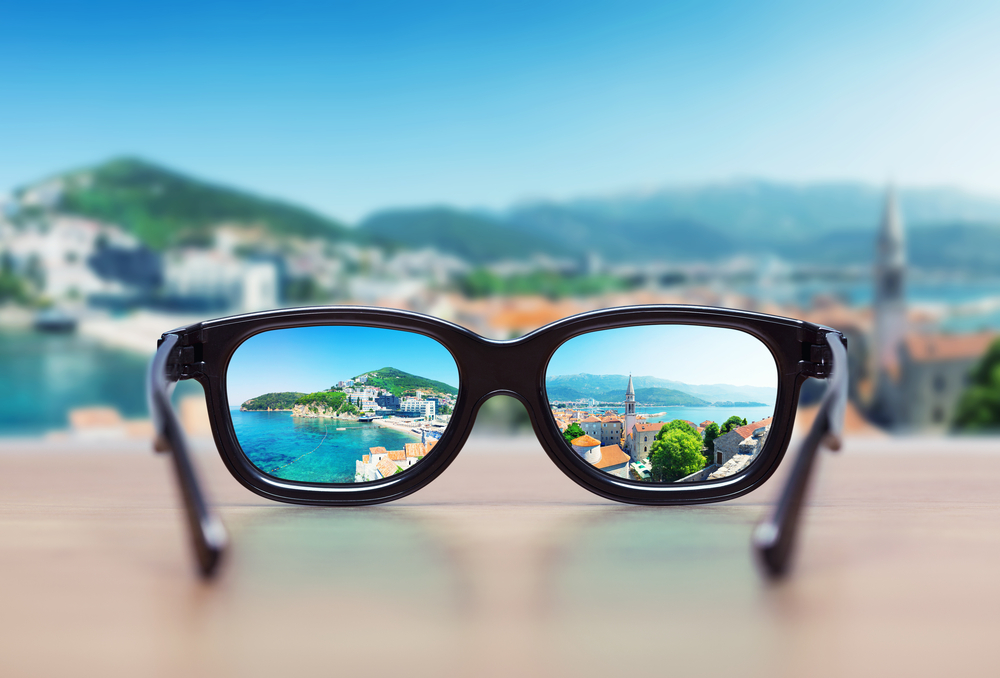 An image of a blurred landscape brought into focus by a pair of glasses